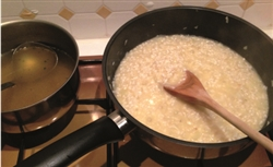 Image shows Spring onion, garlic, and prawn risotto before cooking. There are two pans - one containing chicken stock and one containing rice