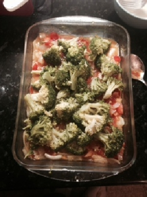 Image shows all the ingredients for Broccoli Mornay in a glass dish ready for cooking.