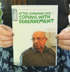 The image shows someone holding up a copy of the booklet After someone dies - coping with bereavement. On the front cover of the booklet, there is an older man wearing glasses, looking slightly to the right.