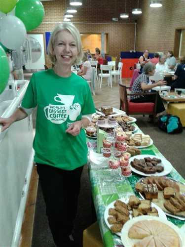 An image of Sue with lots of cakes at her local sports centre