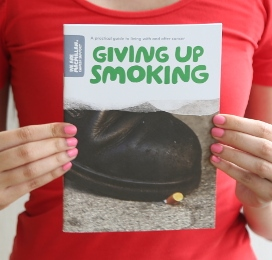 A person holding a copy of the booklet Giving up smoking