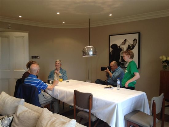 Photograph showing a Macmillan photoshoot in action. There is a cameraman and people having their picture taken