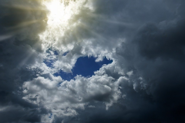 A photo of a cloudy sky, with the sun's rays streaming through.
