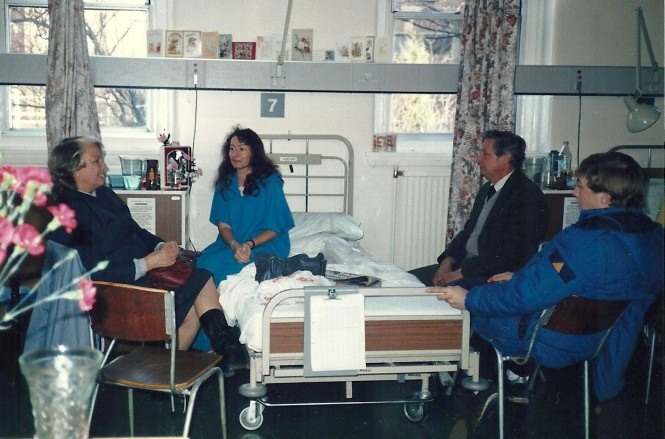 Photo of a Willo's Hospital room, Willo sits on her bed surrounded by 3 friends on chairs